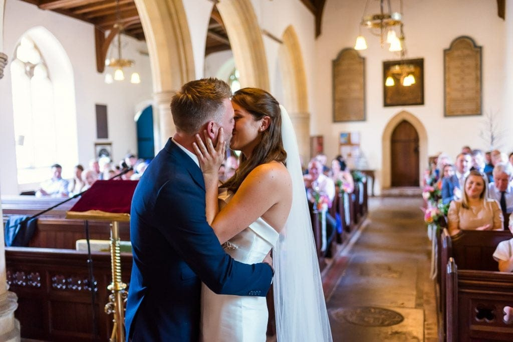 Couples first kiss at their All Saints Church wedding in Horstead.