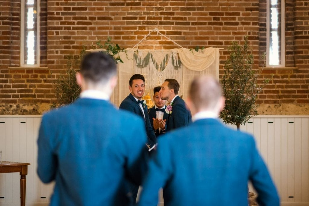 Groomsmen joking around in the Great Barn at Manor Mews